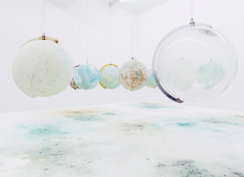 Julian Charrière, We Are All Astronauts, 2013. 13 found globes made of glass, plastic, paper and wood. Steel base with MDF board, dust from globes' surface and international mineral sandpaper. Photo: Martin Agryroglo. Courtesy Julian Charrière.