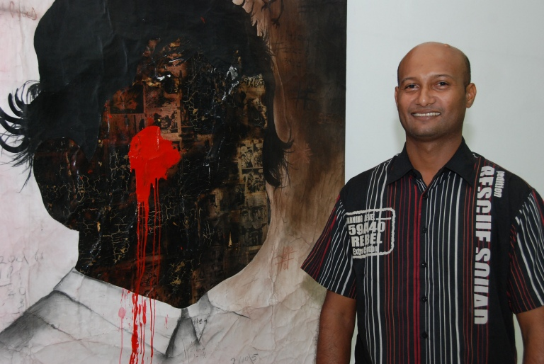 Sunil Puljhun in front of a work from the series 'The Weight of Darkness' / Photo Courtesy Sunil Puljhun