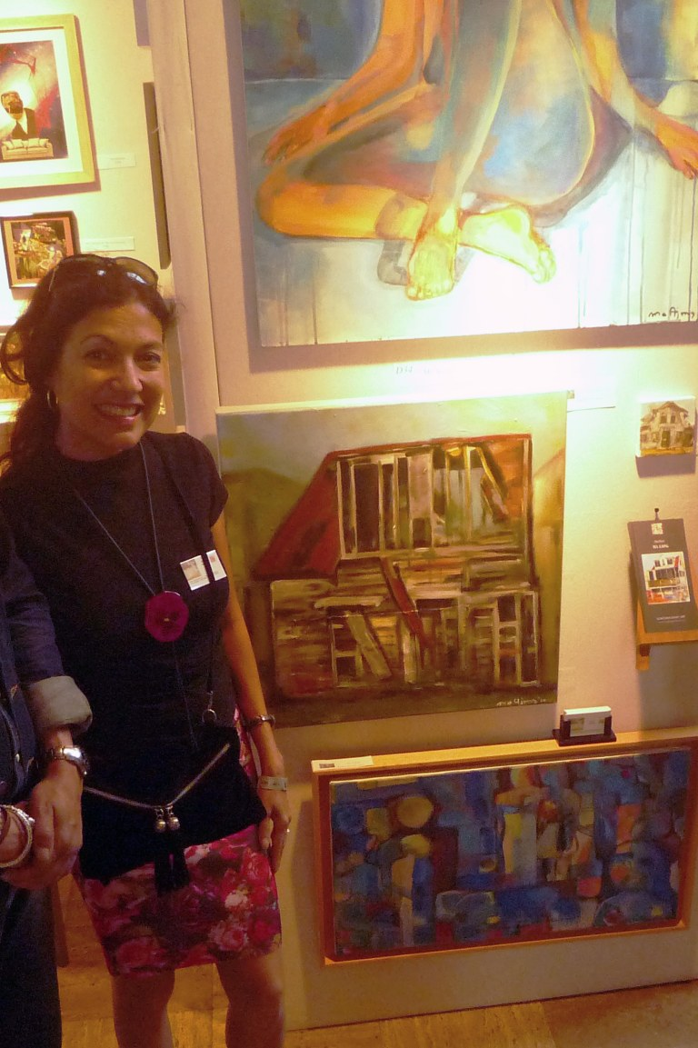 Patricia Ma Ajong in her booth at the International Rotterdam Art Fair 2014, with one of the paintings that is now in the CBK Zuidoost Collection / PHOTO Courtesy Patricia Ma Ajong